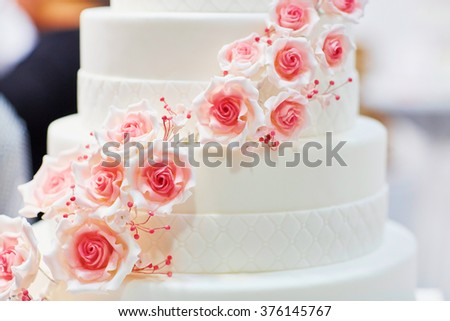 White wedding cake decorated with sugar pink roses - stock photo