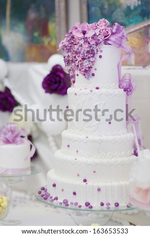 White wedding cake decorated with sugar purple flowers - stock photo
