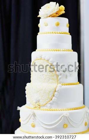 White wedding cake decorated with yellow sugar pattern - stock photo