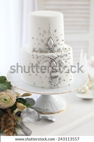 White wedding cake with silver decoration and wedding bouquet with ranunculus - stock photo