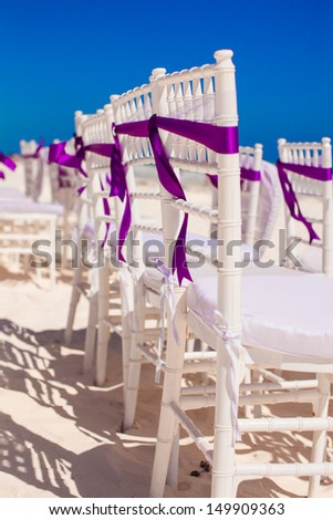 White wedding chairs decorated with purple bows on white sandy beach - stock photo