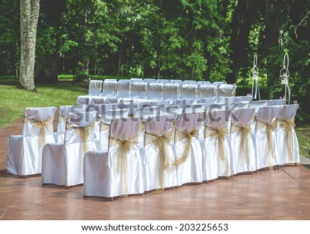 White wedding chairs with brown bows outdoors  - stock photo