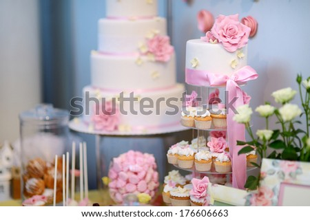 White wedding cupcake cake decorated with pink flowers - stock photo