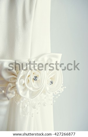 White wedding dress on front of light wall with decorations closeup - stock photo