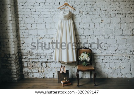 white wedding dress, shoes and a bouquet of white flowers and green against a white brick wall in loft - stock photo