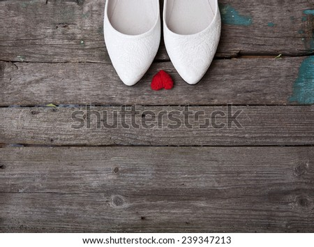 white wedding shoes and red heart on the wood background - stock photo