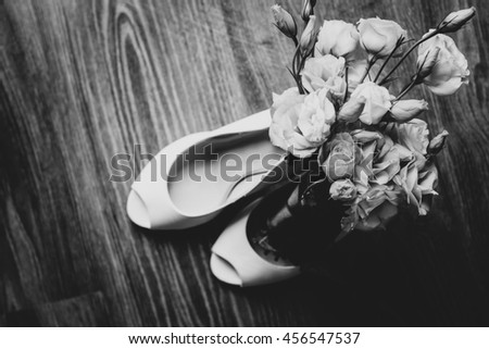 White wedding shoes and wedding bouquet.  - stock photo