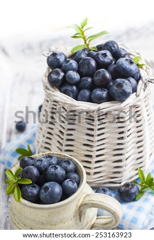 White wicker basket and ceramic jug with fresh blueberries on blue checkered cloth over white painted grunge style wooden table - stock photo