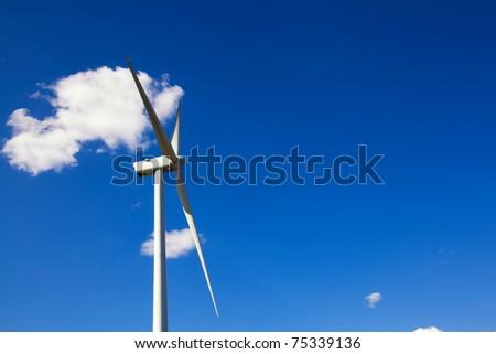 White wind turbine generating electricity on blue sky, alternative energy source - stock photo