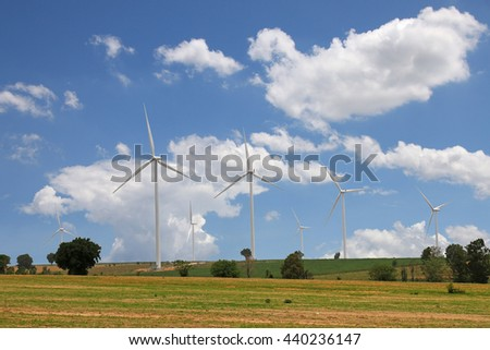 White wind turbines generating electricity and blue sky - stock photo
