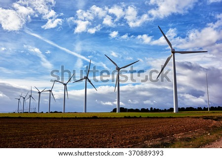 White wind turbines in the field against blue cloudy sky at spring day, electric generators in countryside, windmills in work outside the city - stock photo