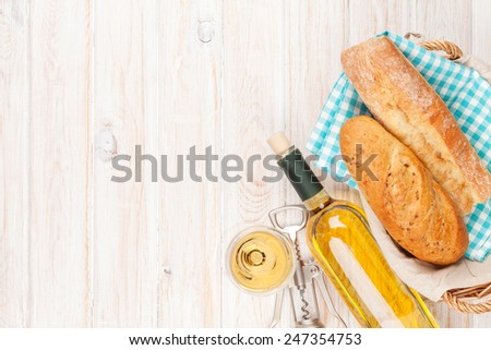 White wine and bread on white wooden table background with copy space - stock photo