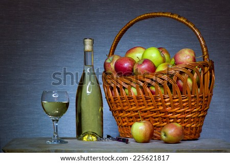 white wine and the basket of apple on the table - stock photo