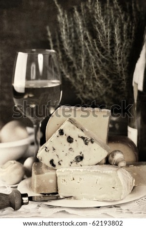 White wine and Various types of cheese on a plate (sepia toned) - stock photo