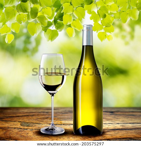 White Wine Bottle and Glass on wood table with summer scene background - stock photo