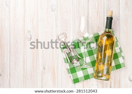 White wine bottle, glass and corkscrew on white wooden table background. Top view with copy space - stock photo