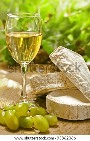 White wine, Brie, Camembert and grape on the wood surface, outdoor - stock photo