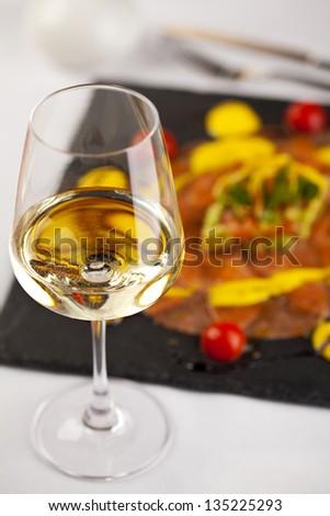 White Wine Glass with Salmon Carpaccio - stock photo