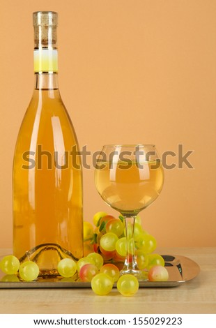 White wine in glass with bottle on salver on beige background - stock photo