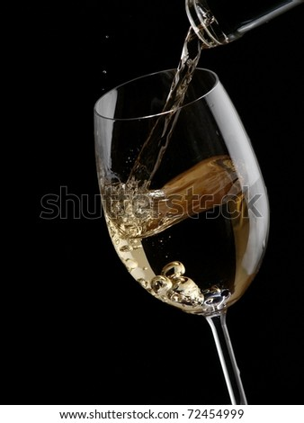 White wine pour in a glass on black background - stock photo