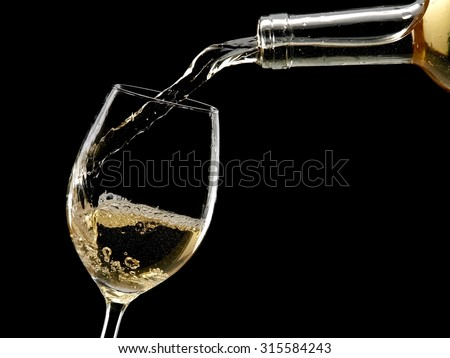 White wine pouring from a bottle - stock photo