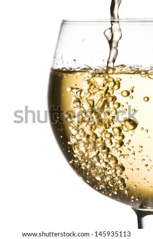 white wine pouring into half glass with space for text  on a white background - stock photo