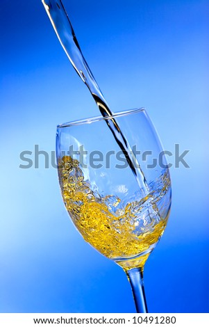 White wine pouring into the glass over blue background - stock photo