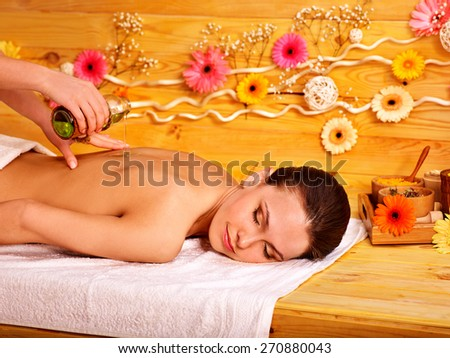 White woman getting  massage in wooden spa. Pouring oil. - stock photo