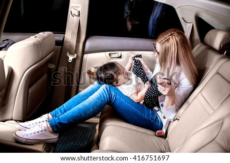 White woman with a child of one year in the light leather car interior have a fun - stock photo