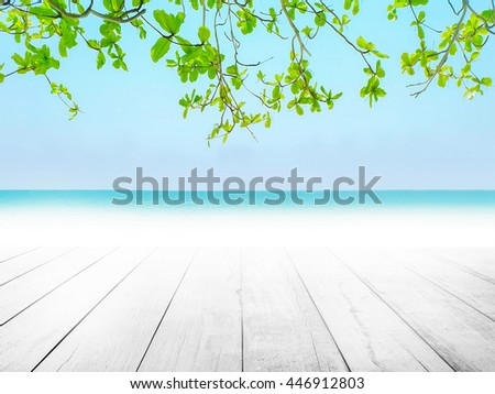 White wood floor with blue surfing wave background. Blue water cool and sky bright. Nature wallpaper blur of sea daytime with green laves in the foreground. Focus to wooden pattern texture stage. - stock photo