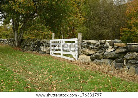 white wood gate by a stonewall in the rural countryside in Connecticut - stock photo