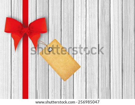 white wooden background with beautiful red bow and tag - stock photo