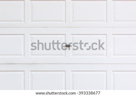 White wooden garage door with small lock. - stock photo