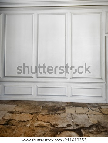 White wooden paneling above a cracked, weathered and worn old flagstone floor in an architectural background - stock photo