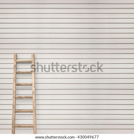 white wooden plank wall with ladder background - stock photo