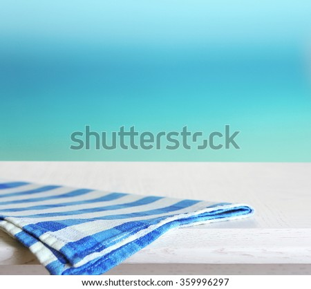White wooden table with napkin on blue background - stock photo