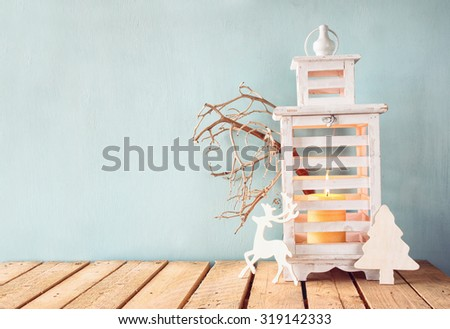 white wooden vintage lantern with burning candle, wooden deer, christmas gifts and tree branches on wooden table. retro filtered image  - stock photo