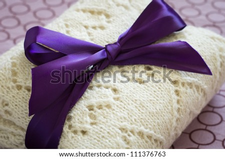 White woolen hand-knit plaid bent and tied with a purple bow, close-up - stock photo