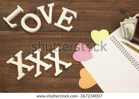 White XXX Love Sign On Wood Background, Opened Notepad With Blank Page And Three Color Heart Sticker, Golden Pen And Male Wallet With Dollar Cash - stock photo