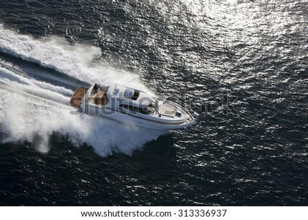 White yacht dashing through the ocean in beautiful evening sunlight - stock photo