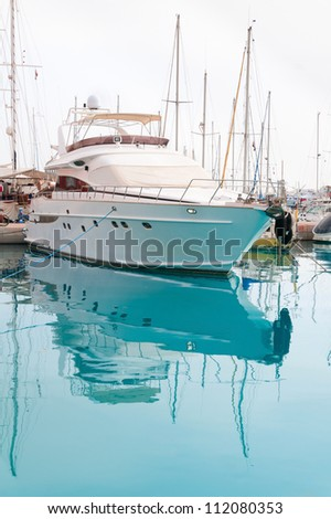 White yacht in a moorage with clean blue water - stock photo