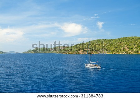 white yacht in Aegean sea on sunny day with green islands at background, Turkey - stock photo