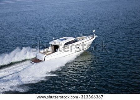White yacht with brown details sailing in the middle of deep blue sea - stock photo