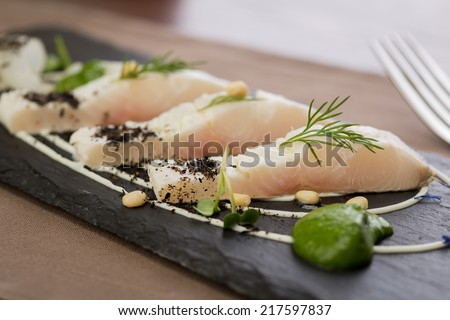 Whitefish fillet served on stone plate - stock photo