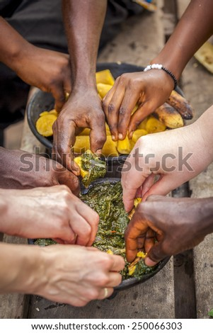 Whites and Blacks eating Palava Sauce and Plantaines. - stock photo
