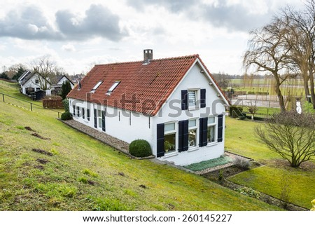 Whitewashed house with shutters and orange tiles at the bottom of a Dutch dike on a cloudy day at the end of the winter season. - stock photo