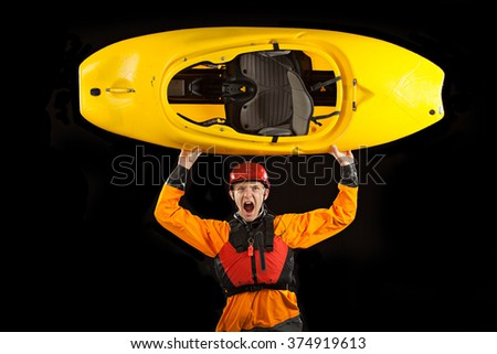 Whitewater kayaker on black background holding boat over his head - stock photo