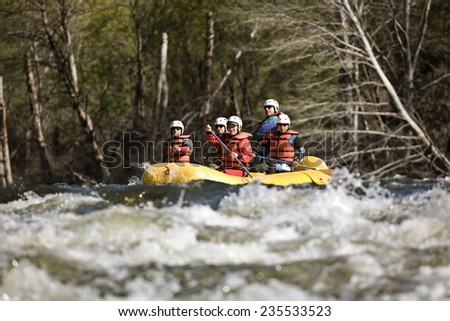 Whitewater Rafters Tackling Rapids - stock photo