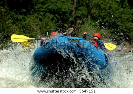 whitewater river raft exploding into the air off wave - stock photo
