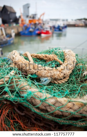 whitstable bay and fishing harbor. nets and rope with trawlers in background - stock photo